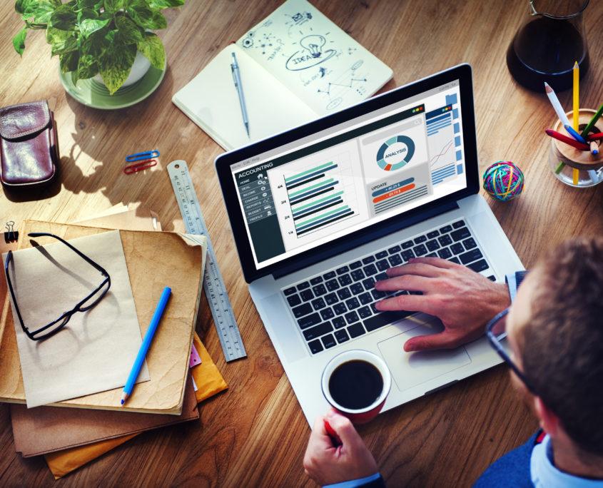 Mężczyzna przy nowoczesnym laptopie analizujący dane księgowe